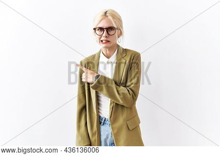 Beautiful caucasian business woman standing over isolated background pointing aside worried and nervous with forefinger, concerned and surprised expression