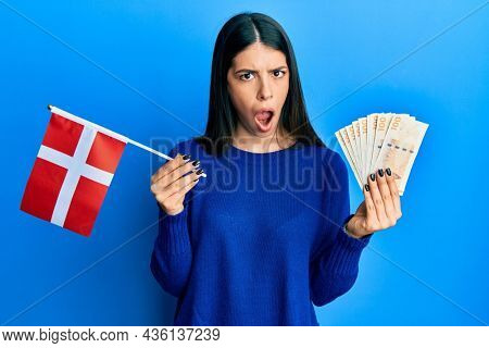 Young hispanic woman holding denmark flag and krone banknotes in shock face, looking skeptical and sarcastic, surprised with open mouth