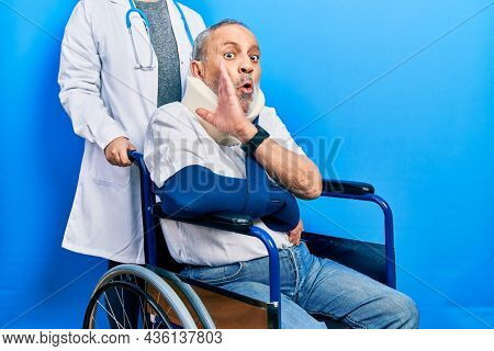 Handsome senior man with beard sitting on wheelchair with neck collar hand on mouth telling secret rumor, whispering malicious talk conversation