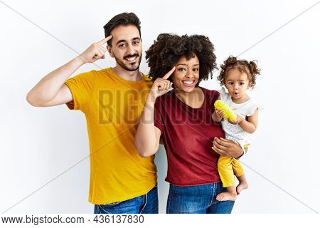 Interracial young family of black mother and hispanic father with daughter smiling pointing to head with one finger, great idea or thought, good memory