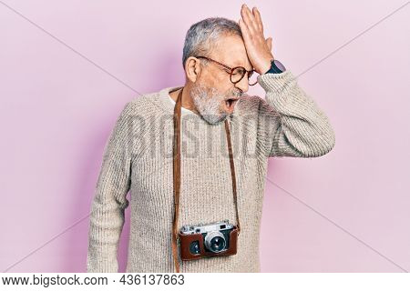 Handsome senior man with beard holding vintage camera surprised with hand on head for mistake, remember error. forgot, bad memory concept.