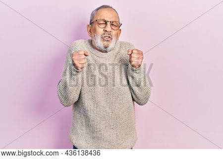 Handsome senior man with beard wearing casual sweater and glasses excited for success with arms raised and eyes closed celebrating victory smiling. winner concept.