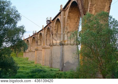 A Long Arched Railway Bridge Over A Green Ravine On A Summer Evening