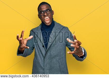 Young african american man wearing business clothes and glasses shouting frustrated with rage, hands trying to strangle, yelling mad