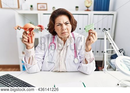 Middle age hispanic doctor woman holding anatomical female genital organ and birth control pills clueless and confused expression. doubt concept.