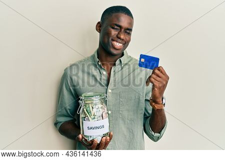 Young african american man holding credit card and jar with dollars winking looking at the camera with sexy expression, cheerful and happy face.