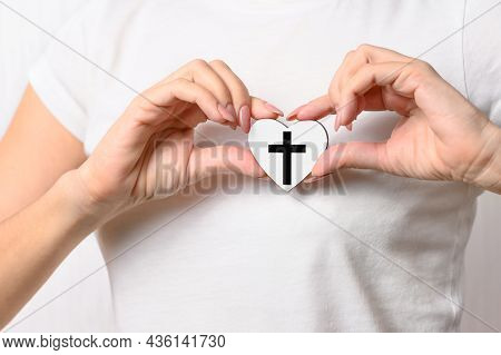 The Girl Holds A Small Heart With A Symbol Of Catholicism On Her Chest. Christianity Concept. Close-
