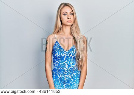 Young beautiful caucasian woman wearing summer dress relaxed with serious expression on face. simple and natural looking at the camera.