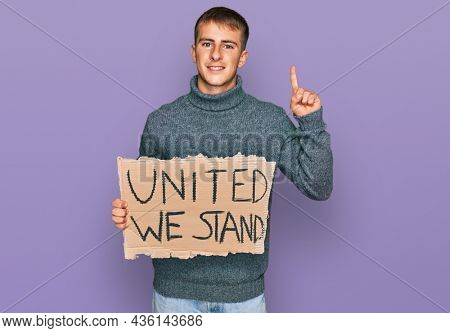Young blond man holding united we stand banner surprised with an idea or question pointing finger with happy face, number one