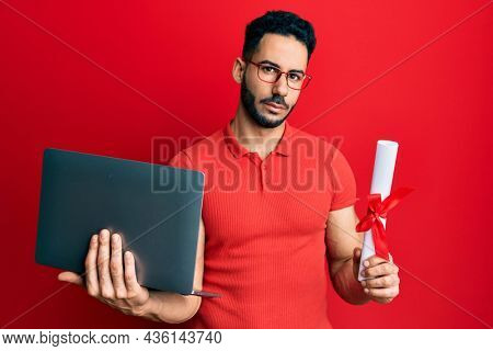 Young hispanic man holding laptop and diploma relaxed with serious expression on face. simple and natural looking at the camera.