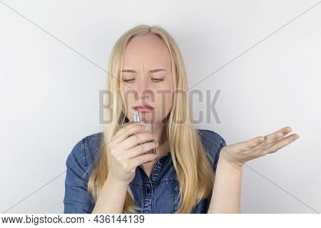 Loss Of Smell. Girl In Front Of The Mirror Sniffs The Perfume And Realizes That She Does Not Feel It