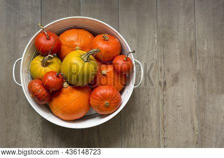Orange Autumn Pumpkins In A White Metal Basin On A Brown Floor Horizontal Top View