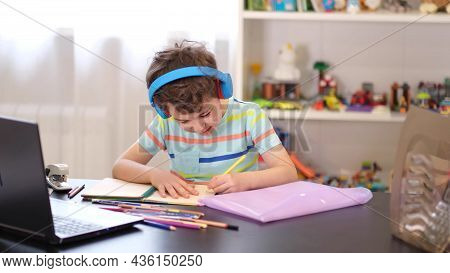 Learn On Your Schedule. Distance Learning Online Education. A Schoolboy Boy Studies At Home And Does