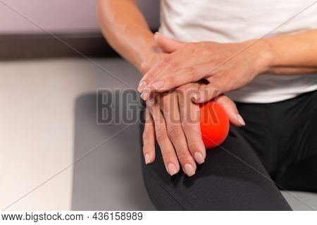 Sporty Slim Caucasian Woman Doing Self-massage Of The Thigh On Fitness Mat With Massage Ball Indoors