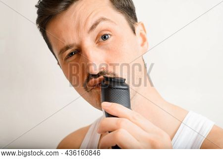 Portrait Of Handsome Brutal Young Man Shaving With Modern Electric Razor And Looking At Camera. Sele