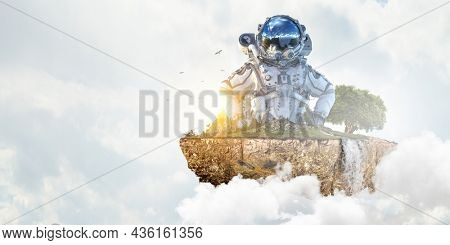 Astronaut against cloudy sky background . Mixed media