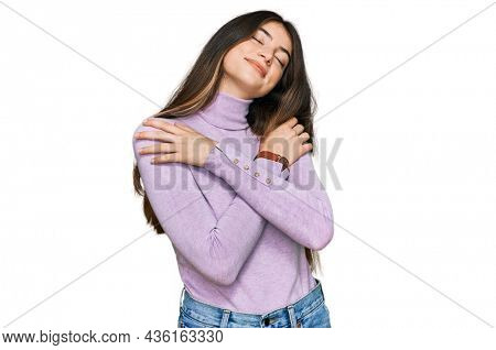 Young beautiful teen girl wearing turtleneck sweater hugging oneself happy and positive, smiling confident. self love and self care