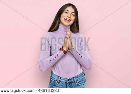 Young beautiful teen girl wearing turtleneck sweater praying with hands together asking for forgiveness smiling confident.