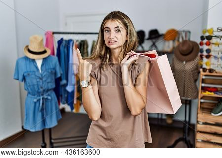 Young blonde woman holding shopping bags at retail shop pointing aside worried and nervous with forefinger, concerned and surprised expression