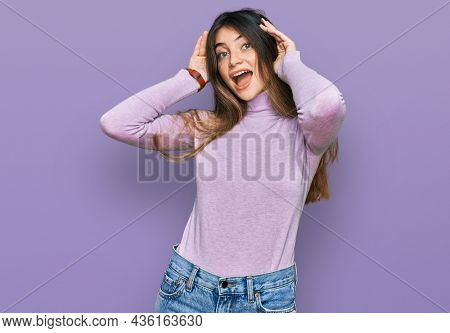 Young beautiful teen girl wearing turtleneck sweater smiling cheerful playing peek a boo with hands showing face. surprised and exited