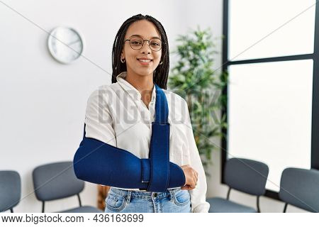 Young african american woman smiling confident injury on arm at clinic waiting room