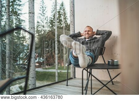 Portrait Of A Sincerely Smiling Middle-aged Man Dressed Open Cardigan, Jeans, And Warm Socks Sitting