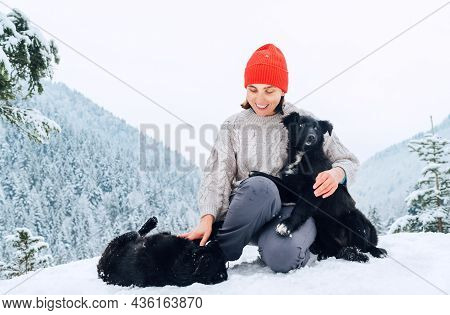 A Young Woman In Warm Clothes Walking Her 2 Dogs In Snowy Mountain Outdoor. Female Laughing, Hugging