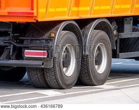 Dump Truck Wheels With All-season Tires On An Asphalt Road. A Close-up Of The Rear Axles Of A Truck.