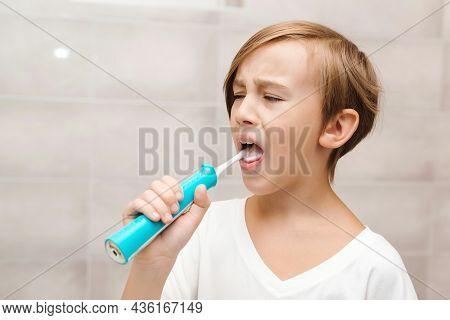 Kid Brushing Teeth With Electic Brush In Bathroom. Dental Hygiene Every Day. Health Care, Childhood