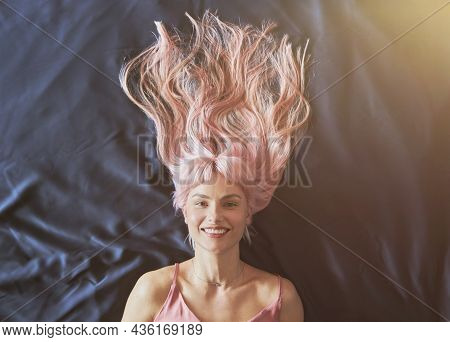 Portrait Of Smiling Woman With Loose Pink Hair Lying On Large Bed With Dark Blue Sheet