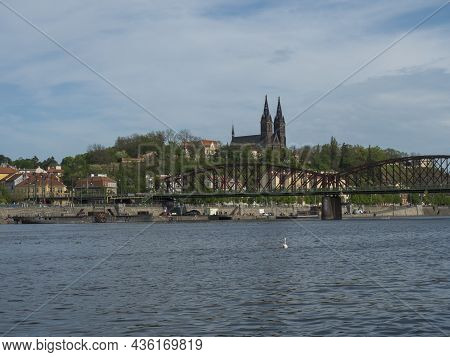 Vltava River Bank With Railway Bridge And Historical Fort Vysehrad With Basilica Of St. Peter And Pa