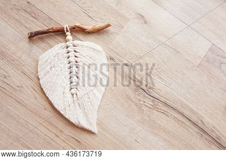 Macrame Leaf  In Natural Color And Thread Windings Lying On A Wooden Table. Cotton Rope Decor Macram