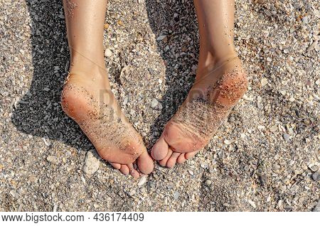 Female Feet On The Background Of Sea Sand. Legs Of A Woman Lying On The Sand Of A Beach.