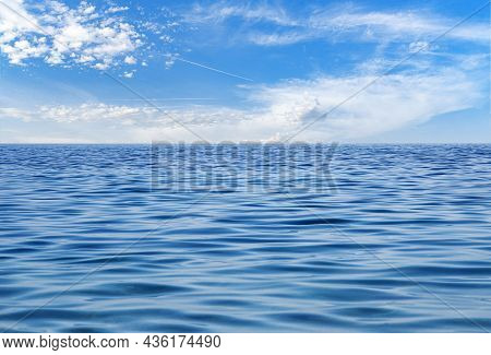 White Clouds On Blue Sky Over Calm Sea With Sunlight Reflection In Sea.