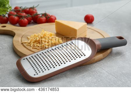 Wooden Board With Grater And Cheese On Grey Table