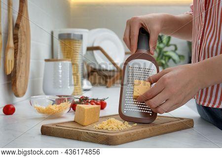Woman Grating Cheese At Kitchen Counter, Closeup