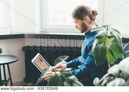 Concentrated Young Man Freelancer Using Laptop And Analysing Data Charts And Graphs In Lounge. Cauca