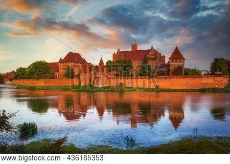 Malbork castle over the Nogat river at sunset, Poland