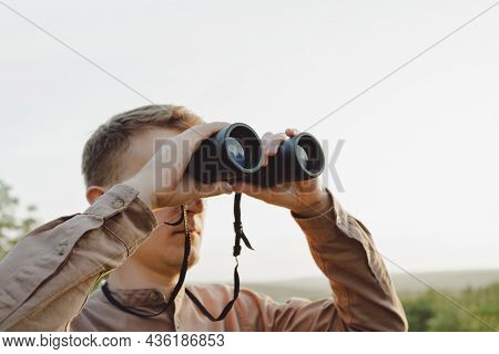 A Young Man Looks Through Binoculars At A Beautiful Hilly Landscape.the Concept Of Hunting, Travel A
