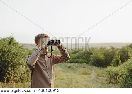 A Man With Modern Binoculars Against The Sky And Green Forest.the Concept Of Hunting, Travel And Out