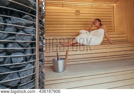 Relaxing Woman Wrapped White Towel Lying And Sweating On The Wooden Bench In Hot Finnish Sauna With