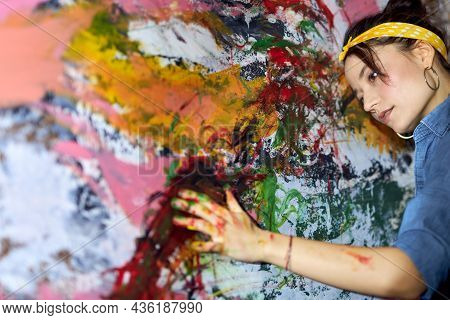 Portrait Of Calm Young Woman, Female Painter Looking Relaxed While Applying Paint On Canvas With Fin