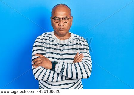 Middle age latin man wearing casual clothes and glasses skeptic and nervous, disapproving expression on face with crossed arms. negative person.