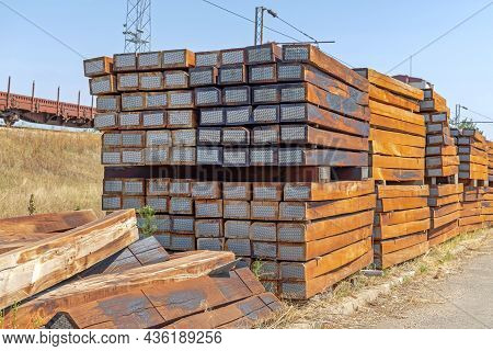 Big Stack Of Old Railroad Ties With Metal Ends