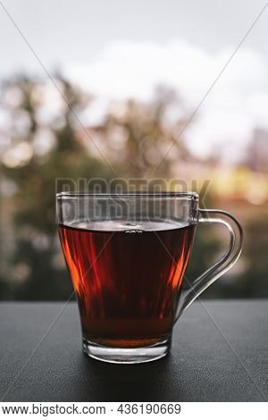 A Cup Of Hot Tea Standing By The Window At Sunset