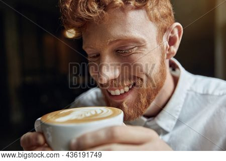 Smiling man in white shirt drinking coffee in cafe or restaurant. Young red haired man is tasting foamy latte. Concept of coffee types and tastes. Bearded stylish guy wearing formal clothes. Daytime.