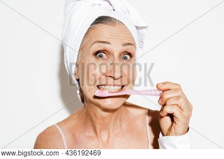 Mature woman wrapped in shower towel grimacing while using toothbrush isolated over white wall