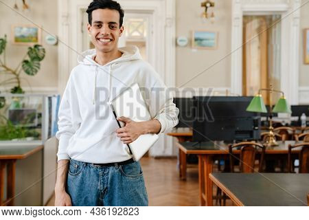 Young middle eastern student man holding laptop and smiling at camera in library