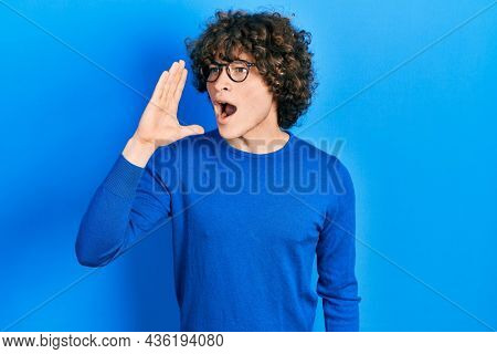 Handsome young man wearing casual clothes and glasses shouting and screaming loud to side with hand on mouth. communication concept.