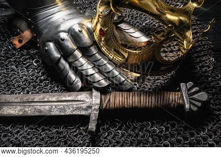Knight Sword And Golden Crown On The Ancient Table Close Up.